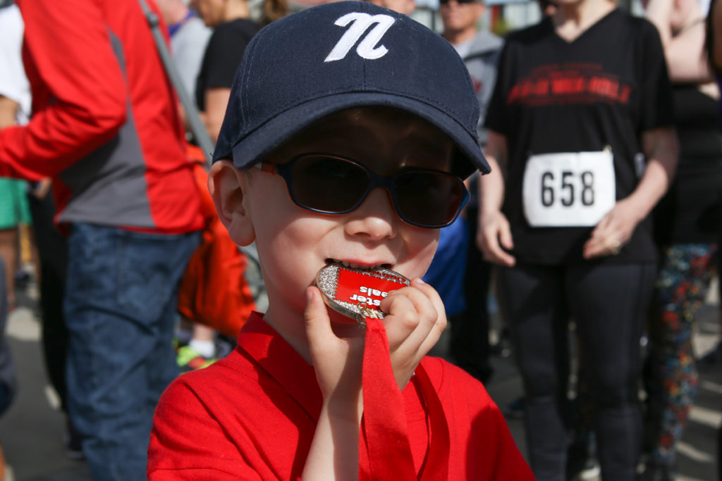 A boy in a hat and sunglasses bites into his medal